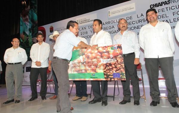 Eduardo Ramírez entregando a cafeticultores un cheque de papel. Foto: Archivo