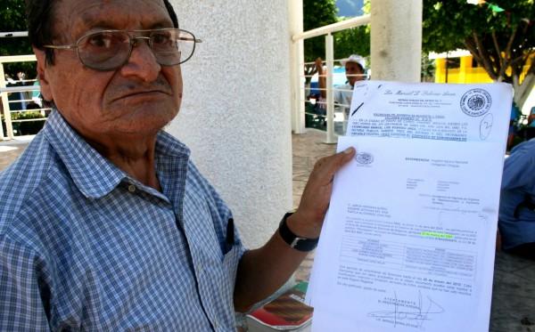 Don Avisaín Solís López exhibe documentos firmados por la CFE en los que se comprometió en 1985 pagar unas tierras afectadas con Chicoasén I y hasta la fecha no cumple. Foto: Isaín Mandujano/Chiapa PARALELO