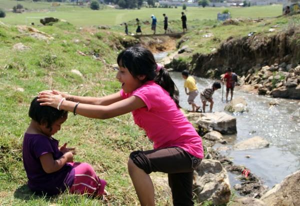 Niñas desplazadas por la violencia  juegan a la orilla de un arroyo, cercano a su refugio en San Cristóbal. Foto: Elizabeth Ruiz