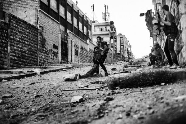 Miembro del FSA ayuda a un compañero herido por el disparo de un francotirador del ejercito Sirio en el barrio de Izaa, Alepo, Siria. Sep. 2012 ©Manu Brabo