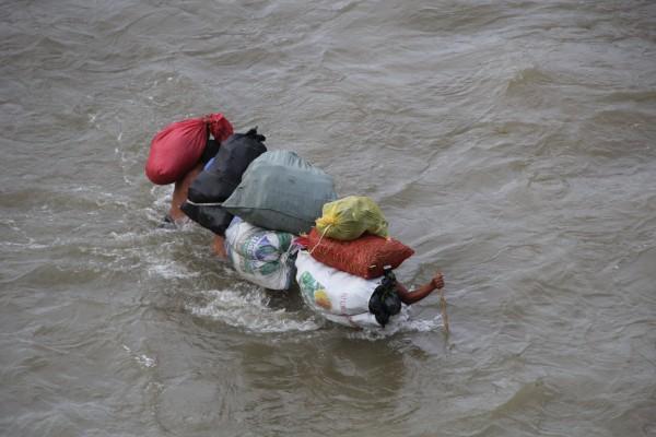 Para vencer la fuerte corriente del Suchiate, cargadores cruzan juntos. Foto: Elizabeth Ruiz
