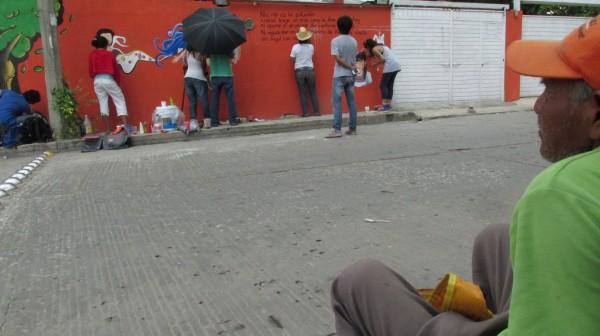 Por más de una hora, este peatón estuvo observando cómo se pintaba el mural, preguntó sobre la obra de la escritora chiapaneca y cuando iba a empezar la lluvia se fue. Ese es el objetivo del mural, que más personas se acerquen a la obra de la escritora comiteca. Foto: Fernando Grajales/Chiapas PARALELO.