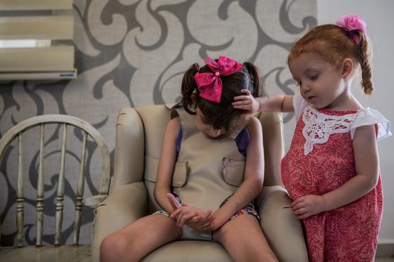Valentina, de 2 años, consuela a su hermana Graciela mientras pasa por una de sus convulsiones en la sala de su casa en Monterrey (Adriana Zehbrauskas / Para The Washington Post).