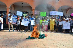 Niños y niñas presencian la quema de sus uniformes verdes en apoyo a sus maestros