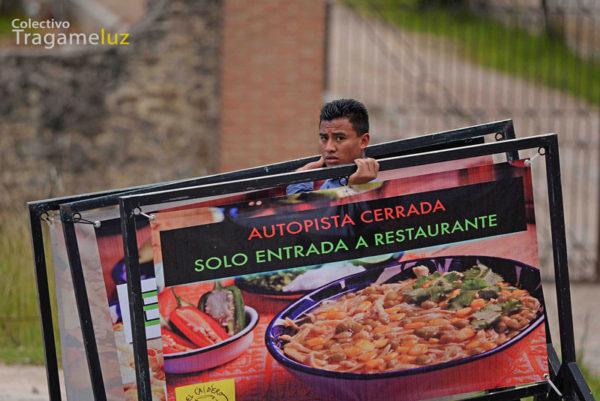 """""""Al final del día"""". Un empleado recoge la publicidad del restaurante donde labora."""