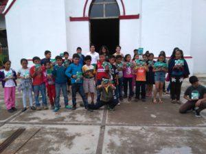 Equipo de difusión repartiendo libros sobre protección civil a niños y niñas de Siltepec.