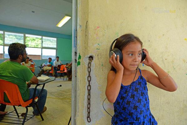 una niña escucha la grabación en vivo de una de las mesas de trabajo en el ejido Francisco I. Madero