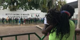 Una madre haitiana sostiene a su hija mientras hace fila afuera de la Estación Migratoria Siglo XXI. Foto de Ángeles Mariscal/Chiapas Paralelo