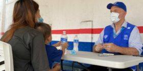 Una madre salvadoreña habla con un trabajador de ACNUR en un centro de registro en el sur de México.  Cortesía: ACNUR/Pierre-Marc Rene