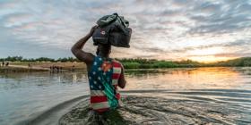 Migrante aprovecha el amanecer para cruzar por provisiones de Estados Unidos a México.  Durante su viaje, migrantes reciben ropa de regalo, lo que visten es más por necesidad que por un mensaje. Foto: Omar Saucedo / Vanguardia